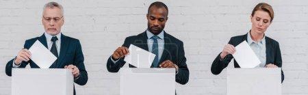 prise de vue panoramique des électeurs multiculturels mettant des bulletins de vote dans les urnes