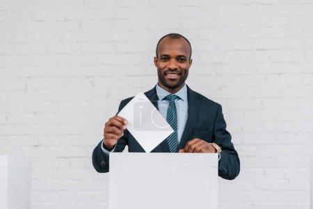 happy african american businessman voting near brick wall