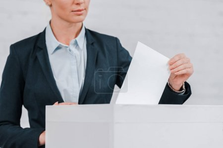 Photo for Cropped view of businesswoman voting near brick wall - Royalty Free Image