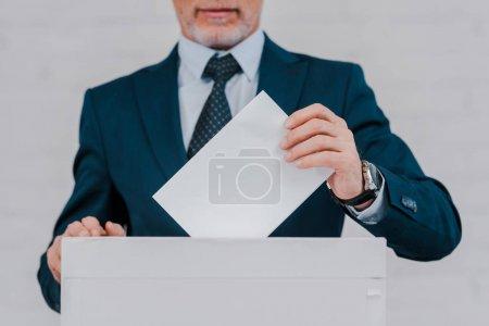 vue recadrée d'un homme d'affaires barbu votant près d'un mur de briques