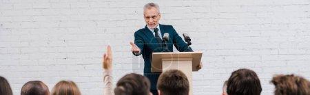 prise de vue panoramique de haut-parleur heureux pointant avec la main au journaliste avec la main levée