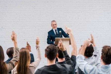 Photo pour Vue arrière de journalistes avec les mains levées près heureux haut-parleur barbu - image libre de droit