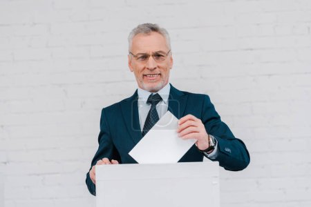 Photo for Cheerful businessman in glasses voting near brick wall - Royalty Free Image