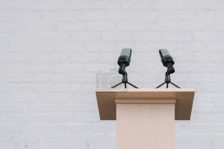 Photo pour Stand en bois avec micros près d'un mur de brique blanche - image libre de droit