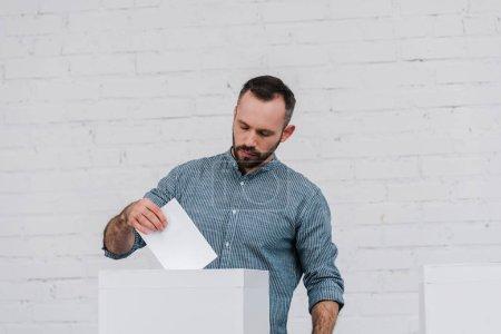 beau votant mettant bulletin blanc dans l'urne