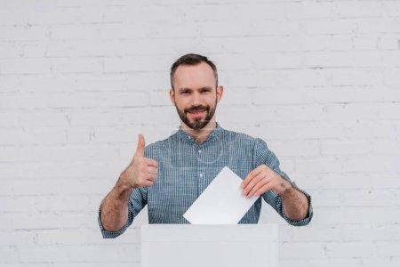 électeur joyeux montrant pouce levé tout en tenant le bulletin de vote blanc
