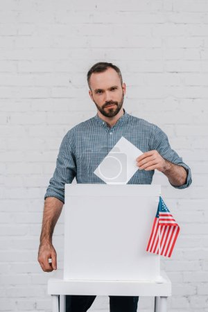 bearded and handsome voter putting blank ballot in voting box near american flag