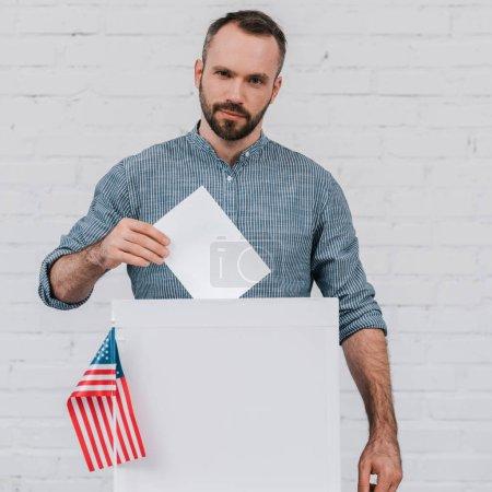 vue recadrée de l'électeur mettant un bulletin de vote blanc dans une urne près du drapeau américain