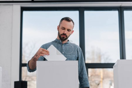 bearded and handsome citizen putting blank ballot in voting box