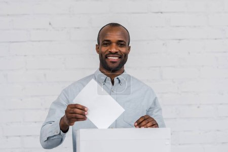 happy african american voter putting blank ballot in voting box