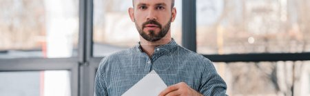Photo for Panoramic shot of handsome voter holding blank ballot and looking at camera - Royalty Free Image