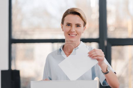 Photo for Happy and attractive citizen voting and looking at camera - Royalty Free Image