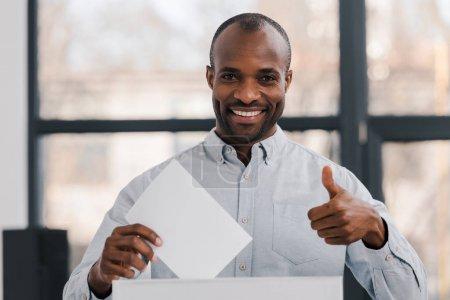 heureux électeur afro-américain tenant un bulletin blanc et montrant pouce vers le haut