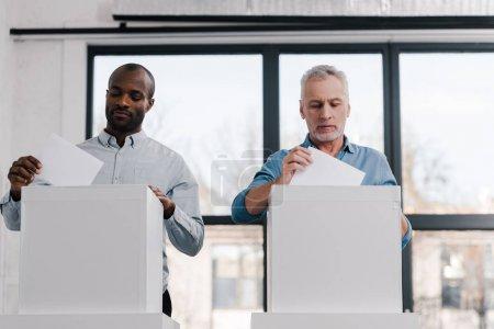 citoyens multiculturels qui mettent des bulletins de vote dans les urnes