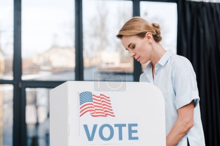 Photo for Side view of attractive woman voting near stand with vote lettering and american flag - Royalty Free Image