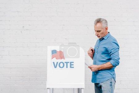 citoyen tenant un stylo en regardant le bulletin de vote près du bureau de vote