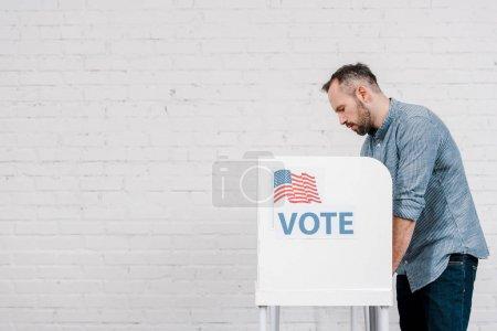 Foto de Vista lateral de los ciudadanos tolerantes que votan cerca de la tribuna con letras de voto y bandera de América - Imagen libre de derechos