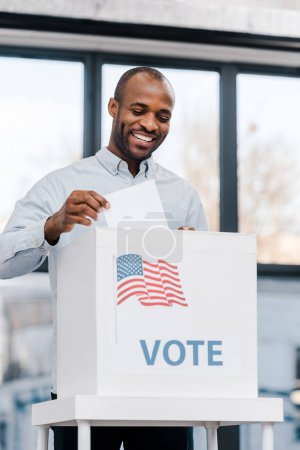 Photo for Cheerful african american man voting and putting ballot in box with flag of america - Royalty Free Image