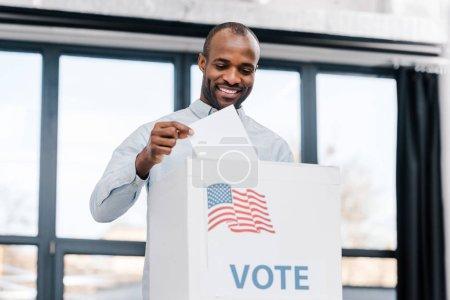 heureux homme afro-américain voter et mettre le bulletin de vote dans l'urne avec le drapeau de l'Amérique