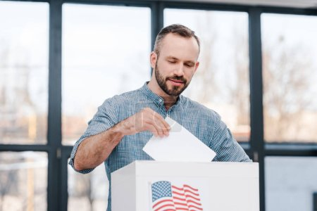 bearded man voting and putting ballot in box american flag