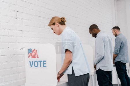 Photo for Selective focus of multicultural citizens voting near brick wall - Royalty Free Image