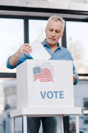 Photo for Bearded man voting and putting ballot in box with vote lettering - Royalty Free Image