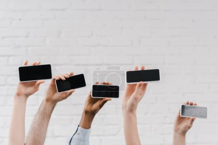 cropped view of multicultural people holding smartphones with blank screen near brick wall