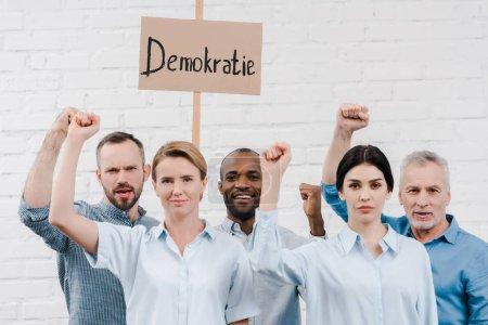 Foto de Grupo de personas multiculturales haciendo gestos cerca de pancarta con letras demokratie - Imagen libre de derechos