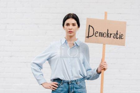 Foto de Mujer con pancarta demokratie y de pie con la mano en cadera cerca de la pared de ladrillo. - Imagen libre de derechos