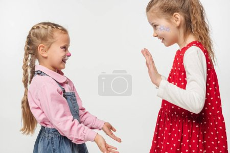 Photo pour Amis excités avec museau de chat et peintures florales sur les visages se serrant les mains les uns avec les autres isolés sur le blanc - image libre de droit
