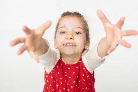 Photo pour Enfant adorable avec peinture florale sur le visage tendant les mains à la caméra isolé sur blanc - image libre de droit