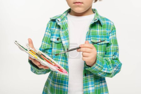 Photo for Cropped view of boy in checkered shirt holding palette and paintbrush isolated on white - Royalty Free Image