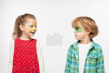Photo pour Amis mignons avec museau de chat et masque de gecko peintures sur les visages se regardant les uns les autres isolés sur blanc - image libre de droit