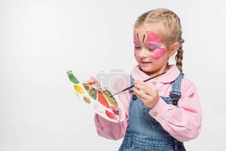 Photo pour Adorable enfant avec peinture papillon sur palette tenant le visage et pinceau isolé sur blanc - image libre de droit