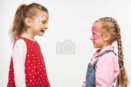 Photo pour Vue latérale d'amis souriants avec museau de chat et peintures papillon sur des visages se regardant les uns les autres isolés sur du blanc - image libre de droit