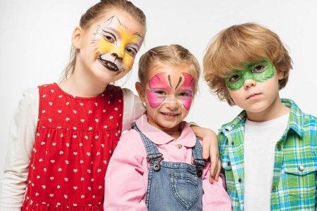Foto de Amigos sonrientes con coloridas pinturas de cara que miran a la cámara aislada sobre blanco. - Imagen libre de derechos