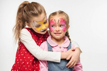Foto de Joven adorable con muzzle de gato pintando en la cara abrazando a un amigo con máscara de mariposa pintada aislada sobre blanco. - Imagen libre de derechos