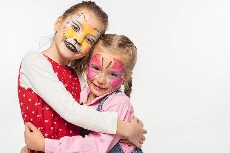 Foto de Niños lindos con boquilla de gato y pinturas a mariposas en rostros que abrazan mientras miran la cámara aislada en blanco. - Imagen libre de derechos