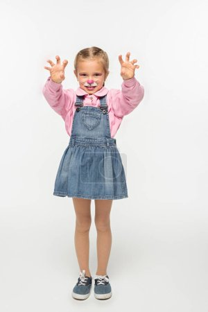 full length view of cute kid with cat muzzle painting on face showing frightening gesture while looking at camera on white background