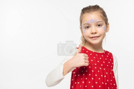 Photo for Adorable child with floral painting on face smiling at camera and showing thumb up isolated on white - Royalty Free Image
