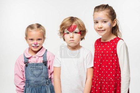 Foto de Niños alegres y niños ofendidos con coloridos cuadros de cara que miran a la cámara aislada en blanco. - Imagen libre de derechos