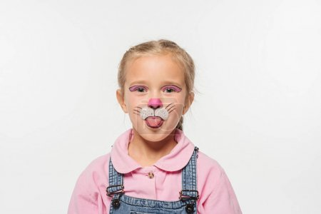 cheerful kid with cat muzzle painting on face sticking tongue out while looking at camera isolated on white