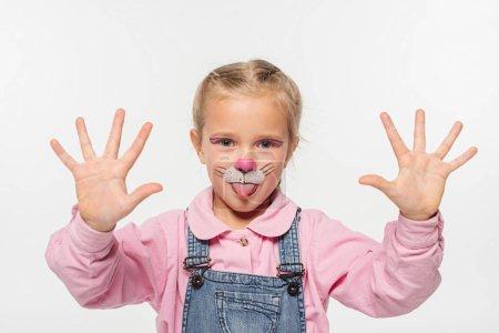 Foto de Niño alegre con pintura de boquilla de gato en la cara mostrando palmas mientras se mira la cámara aislada en blanco. - Imagen libre de derechos