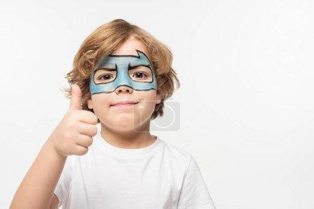 Photo pour Garçon gai avec un masque de super-héros peint sur le visage montrant le pouce levé en regardant la caméra isolée sur blanc - image libre de droit