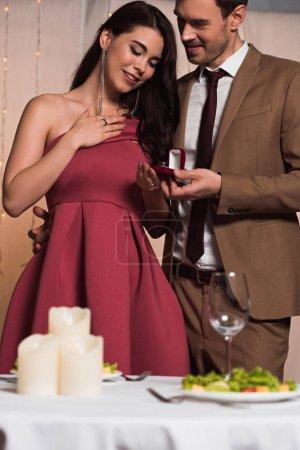 Photo pour Bel homme élégant faisant la demande en mariage à petite amie heureuse dans le restaurant - image libre de droit