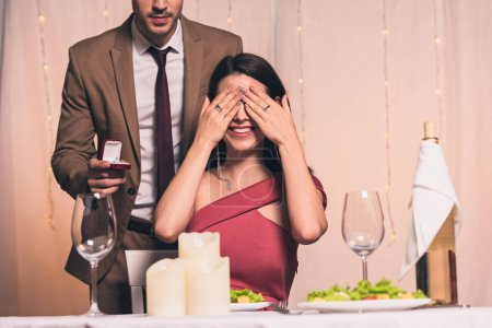 Photo for Elegant man holding wedding ring near happy girlfriend sitting at served table and covering eyes with hands - Royalty Free Image