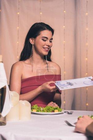 Photo pour Vue partielle du serveur donnant menu à attrayante et élégante fille dans le restaurant - image libre de droit