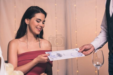 Photo for Cropped view of waiter giving menu to attractive, elegant girl in restaurant - Royalty Free Image