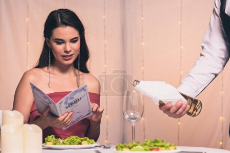 Photo for Attractive, elegant girl reading menu while waiter pouring white wine in glass - Royalty Free Image