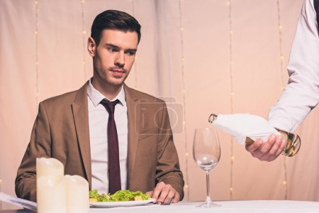 Photo for Cropped of waiter pouring white wine in glass near handsome, elegant man sitting in restaurant - Royalty Free Image